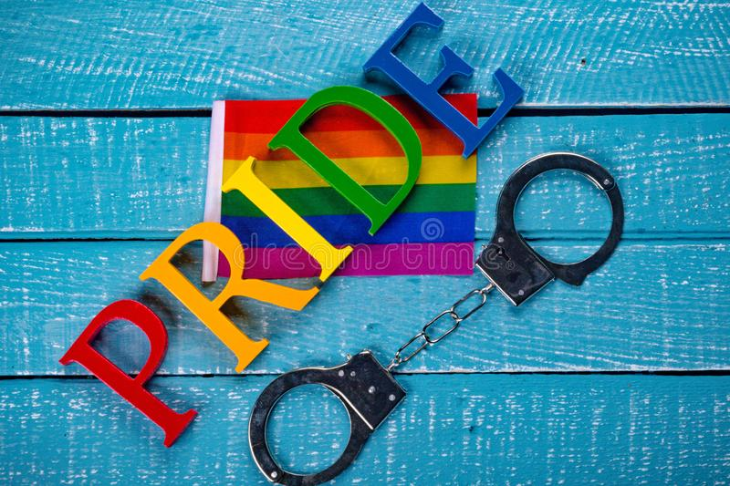 Top down photo of Gay Pride concept. Top down image showing PRIDE spelt in coloured letters on a blue wooden background with a flag and handcuffs royalty free stock photography