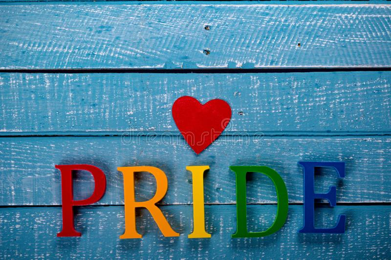 Top down photo of Gay Pride concept. Top down image showing Pride spelt in coloured letters on a blue wooden background with a red heart royalty free stock image