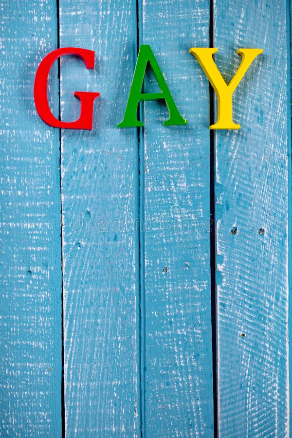 Top down photo of Gay Pride concept. Top down image showing GAY spelt in coloured letters on a blue wooden background royalty free stock image