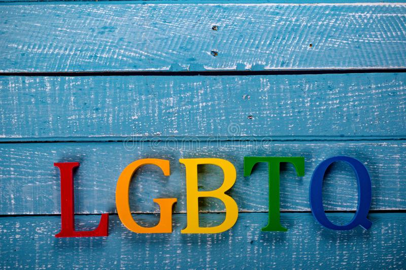 Top down photo of Gay Pride concept. Top down image showing LGBTQ spelt in coloured letters on a blue wooden background stock image