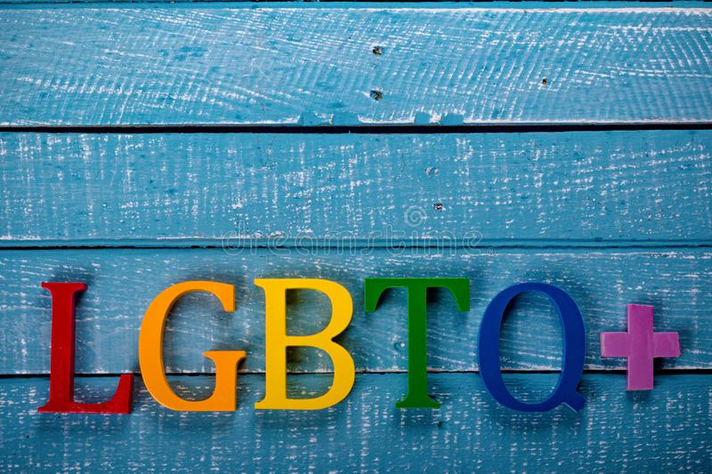 Top down photo of Gay Pride concept. Top down image showing LGBTQ+ spelt in coloured letters on a blue wooden background royalty free stock photos