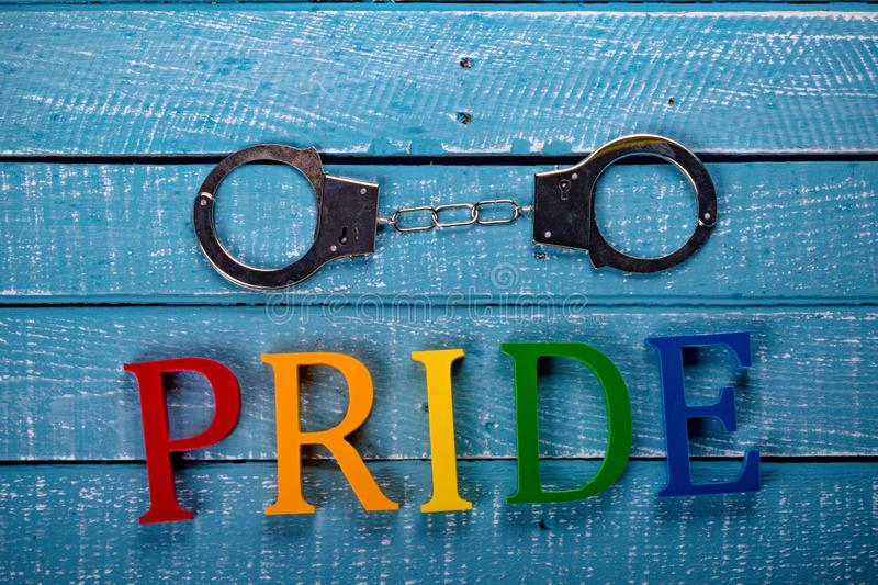 Top down photo of Gay Pride concept. Top down image showing Pride spelt in coloured letters on a blue wooden background with handcuffs stock images