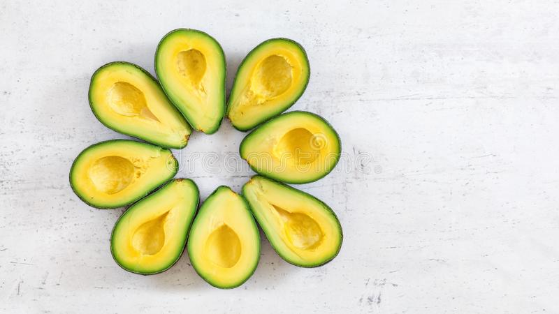 Top down view, 8 avocado halves arranged in circle on white board, banner with space for text right stock image