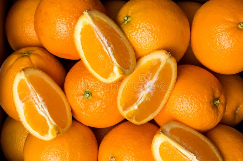 Case of fresh navel oranges. A top down view of a case of fresh navel oranges with an orange cut into quarters on top stock photo