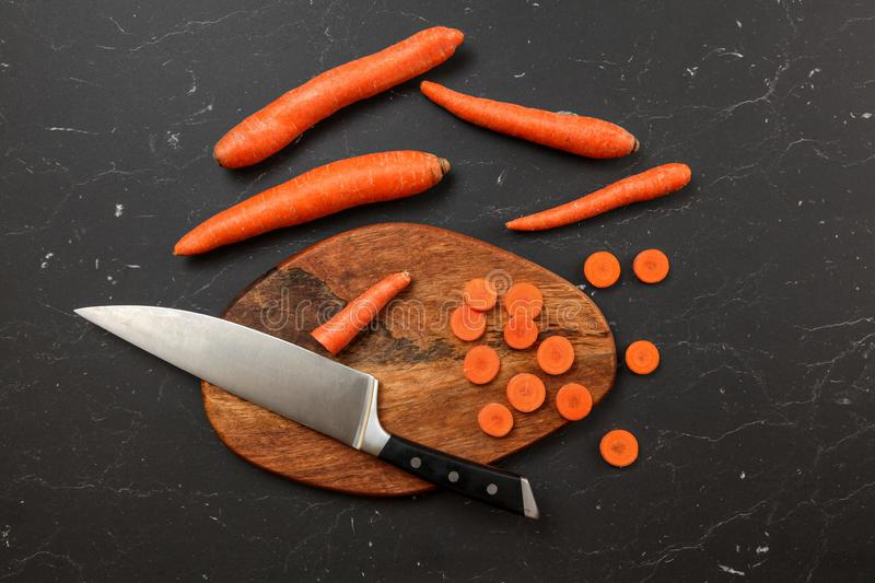 Top down view, chopping board, chef knife, and carrots, some of them cut in small circles, on black marble desk royalty free stock photography