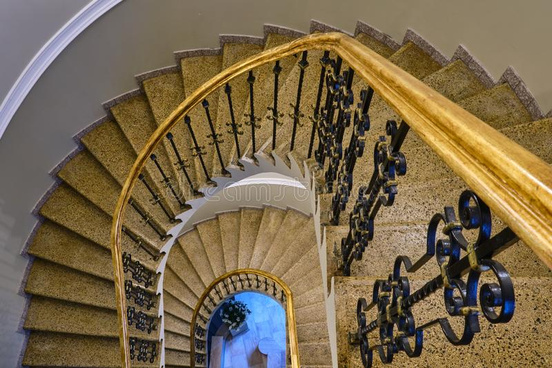 Top down view of elegant, golden, spiral staircase royalty free stock images