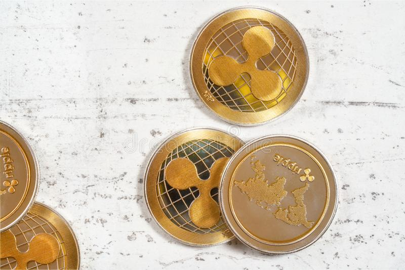 Top down view, golden XRP - ripple cryptocurrency - coins on white stone board.  stock photo