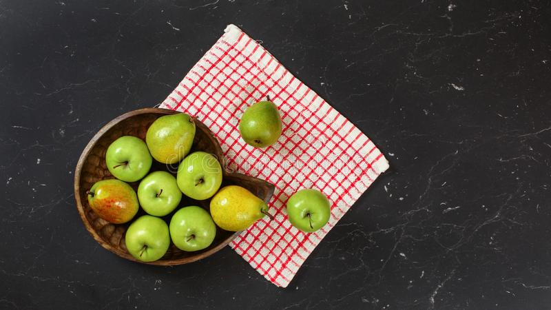 Top down view, green apples and pears in wooden carved bowl, red chequered tablecloth and black marble board under.  stock images