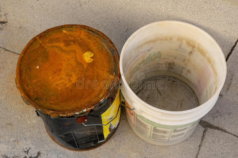 Top-down view of an old rusty metal bucket and a dirty white plastic bucket, closeup stock photo