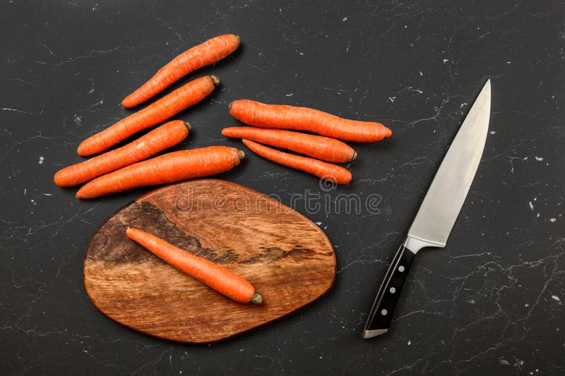 Top down view, orange carrot, chopping board and chef knife next to it, on black marble board royalty free stock photo