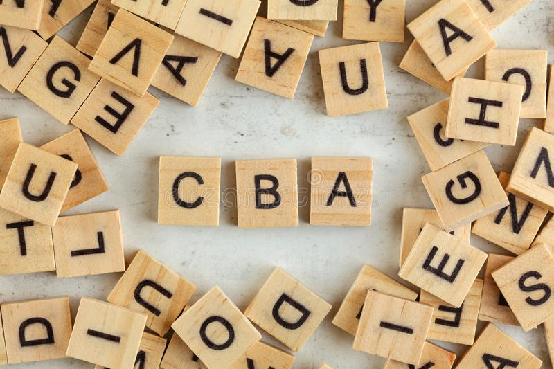 Top down view, pile of square wooden blocks with letters CBA stands for Cost Benefit Assessment on white board stock images