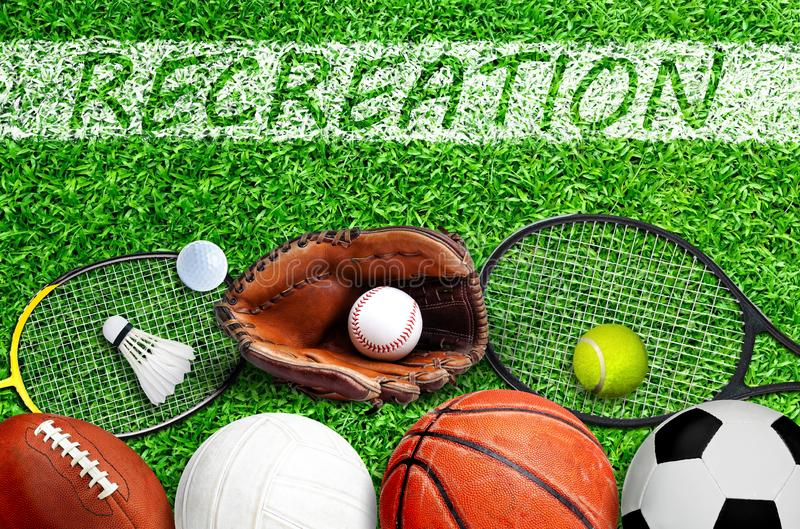 Sports Equipment on Field With Recreation Painted on Grass. Top down view of popular sports equipment on field with RECREATION text painted on line marking royalty free stock images