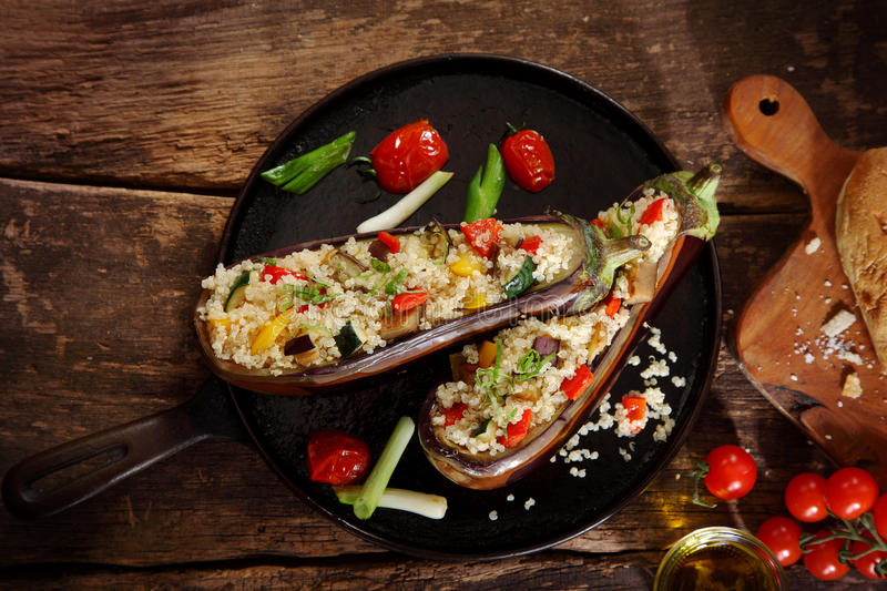 Top down view of a stuffed aubergine with couscous or quinoa. On a brown vintage wooden background royalty free stock photos