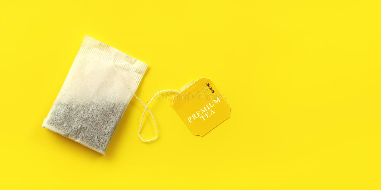 Top down view, tea bag on yellow board, wide banner with space for text on right side stock photo