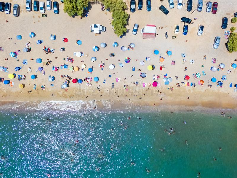 Top down view of a very crowded beach in Athens, Greece. Top down view of a very crowded beach with umbrellas and people during the summer time in Athens, Greece stock photography