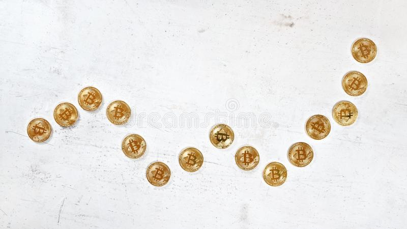 Top down view, white stone board desk with golden bitcoin coins in shape of rising graph - bullish cryptocurrency market royalty free stock photo