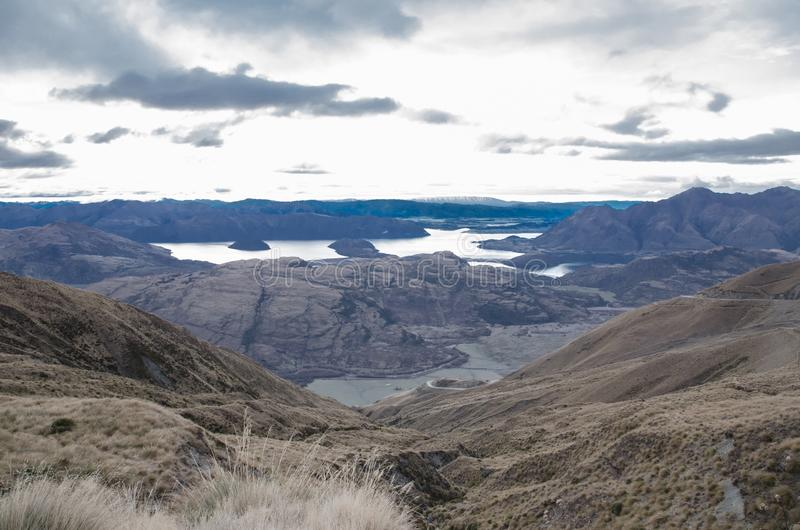 The top of the dry mountain showing mountain with clouds and the lake in the middle of them at South Island, New Zealand. On the top of the dry mountain showing stock photography