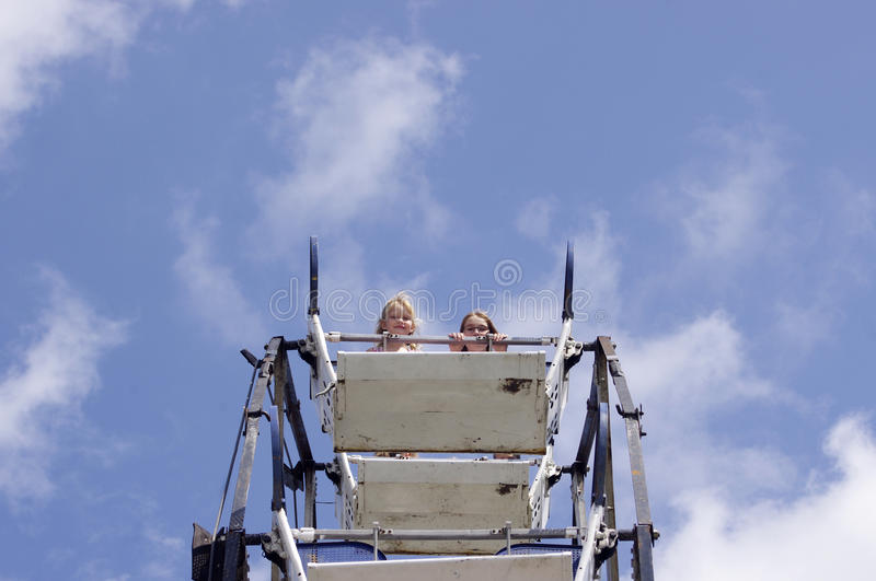 Top of Ferris wheel. Two girls at top of Ferris wheel in a blue sky royalty free stock image