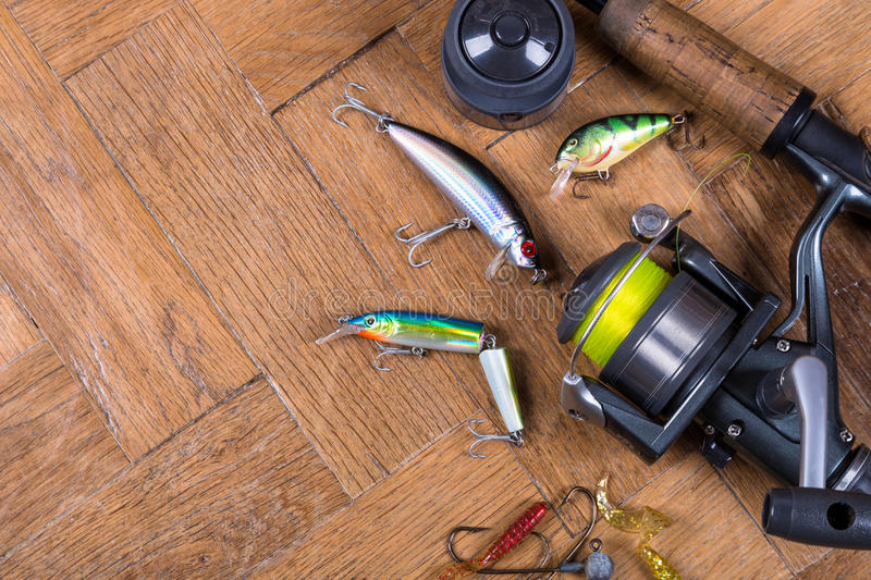 Top fishing baits wobblers, rod with reel. Top fishing bait wobbler, rod and reel with line on wooden background royalty free stock image
