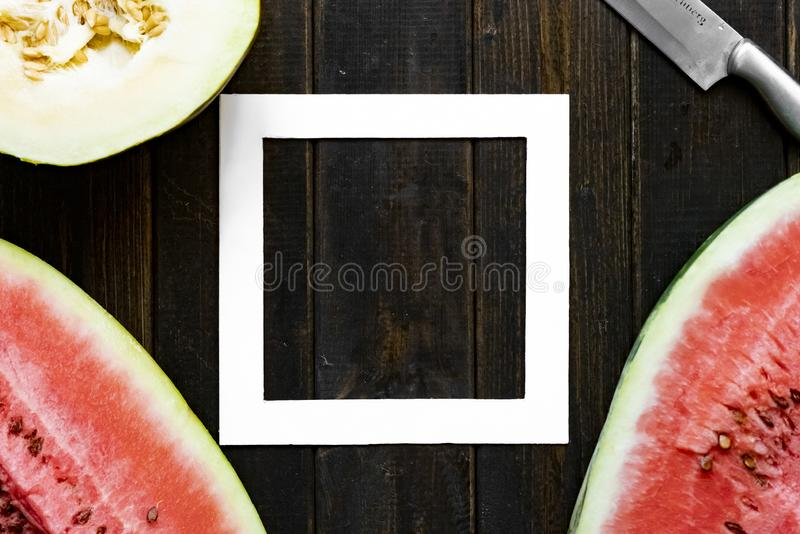 Top flat lay of fresh melon and watermelon copy space with white square frame on a wooden surface f stock image