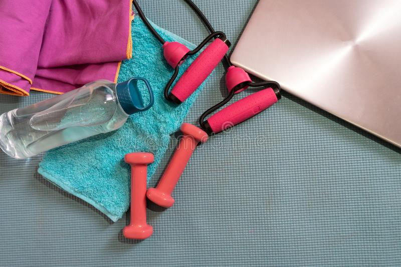 Top or flat lay view of pink dumbbells, towel, water bottle, jumping rope and computer with copy space area on green yoga mat. royalty free stock images