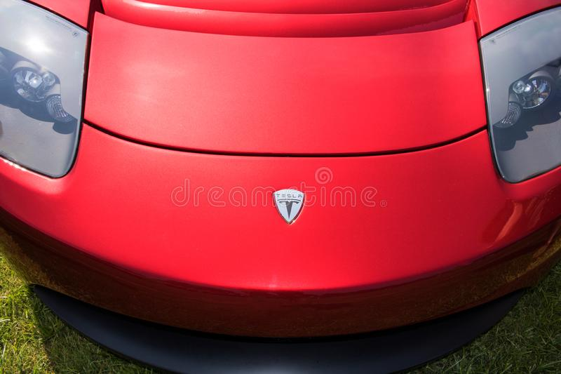 Red Tesla Roadster Sports Car Rear Front. Top front view of a bright red Tesla Roadster sports car parked in a green grassy field royalty free stock photo