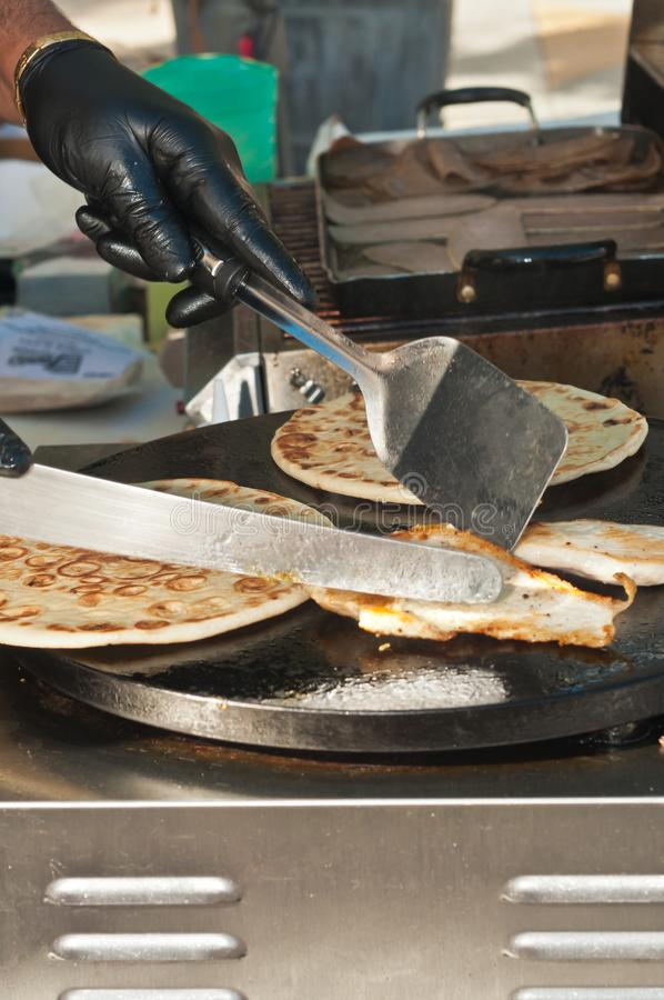 Greek vender grilling chicken and flatbread at a tropical farmers market royalty free stock photography