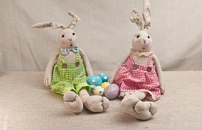 Two stuffed, baby rabbits with four colored, easter eggs royalty free stock photography