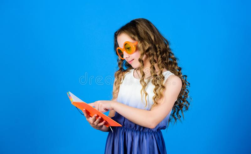 Top funny books to read. Beach reads for summer. Kid likes reading book. Popular vacation books. Great books for summer. Vacation. Girl in sunglasses hold book royalty free stock photo