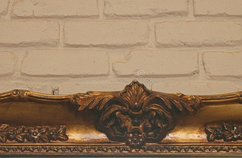 TOP OF GILDED DECORATIVE PICTURE FRAME AGAINST A PAINTED BRICK WALL royalty free stock photography