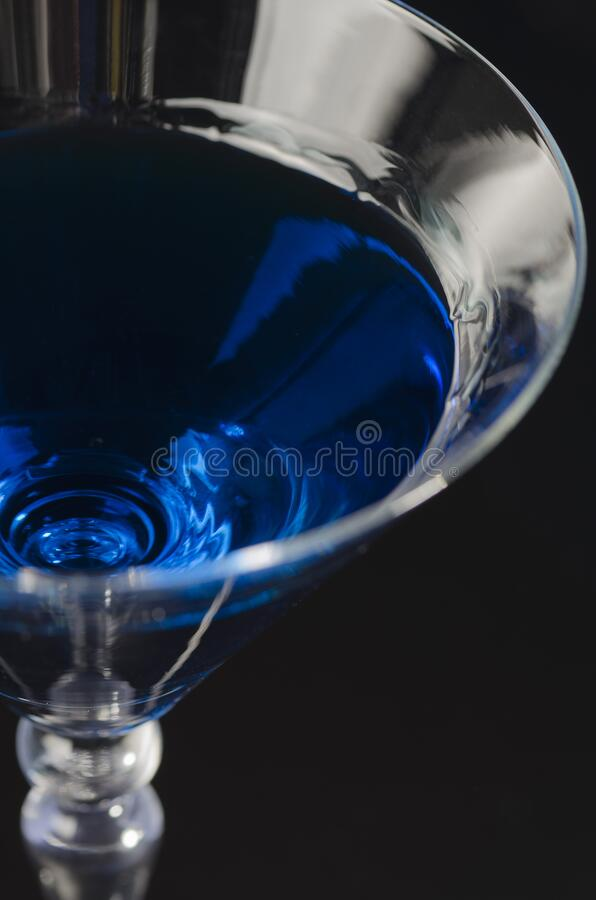Top of the glass with a blue drink on a black background stock images