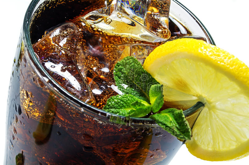 Top of a glass of cola or coke with ice cubes, lemon slice and peppermint garnish stock photo