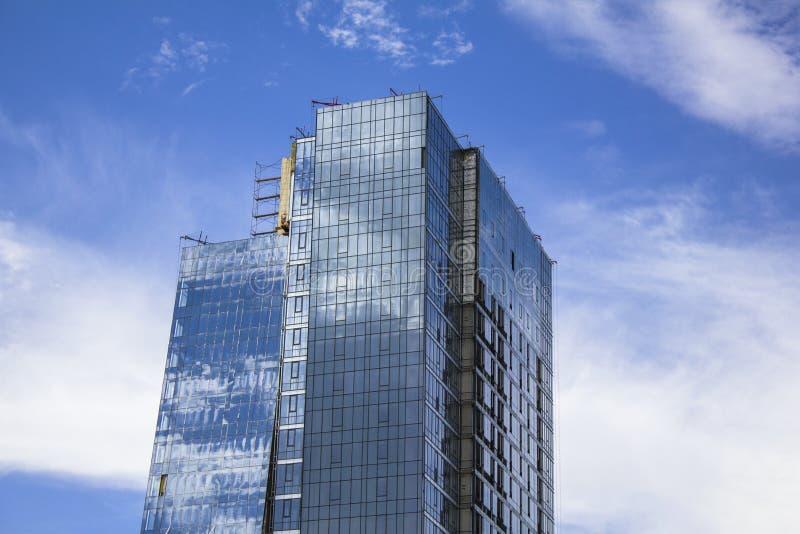 Top of a glass skyscraper under construction against a blue sky. A top of a glass skyscraper under construction against a blue sky stock photo