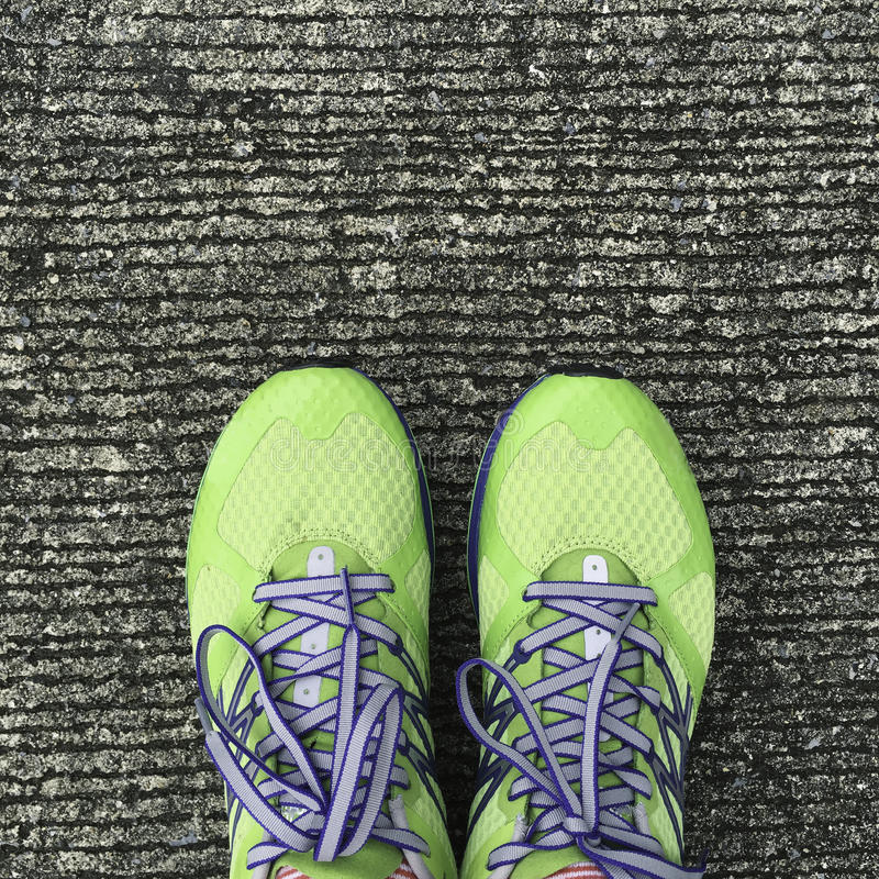 Top of green exercise shoes with concrete background stock images