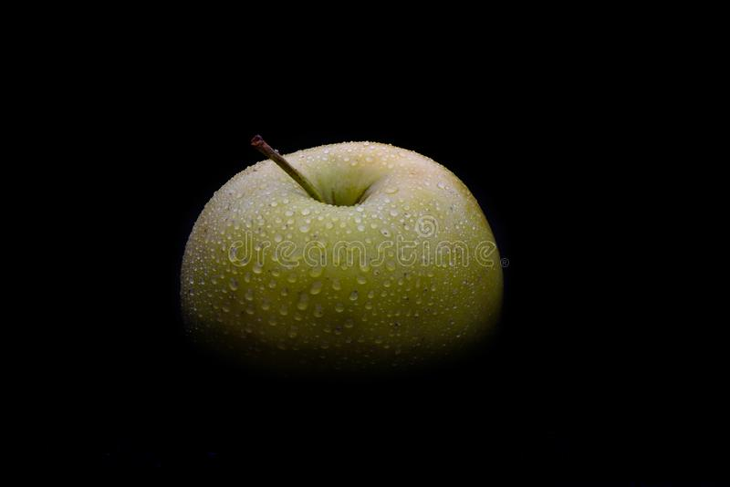 Top of a green ripe apple in drops of water on a black backgroun royalty free stock photography