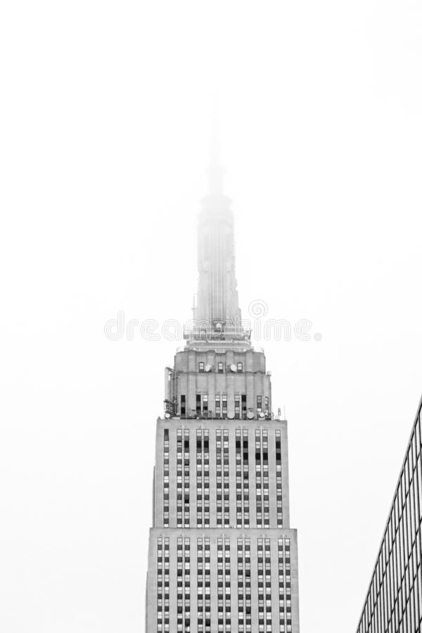 Top half of Empire State Building with tower lost in fog. stock image