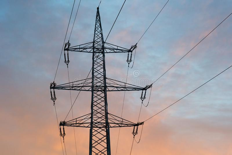 Top Hamper of a 220 kilovolt Electric Power Pylon in Morning Light. Top Hamper of a 220 kilovolt Electric Power Pylon lattice boom with 6 phases and one optical stock image