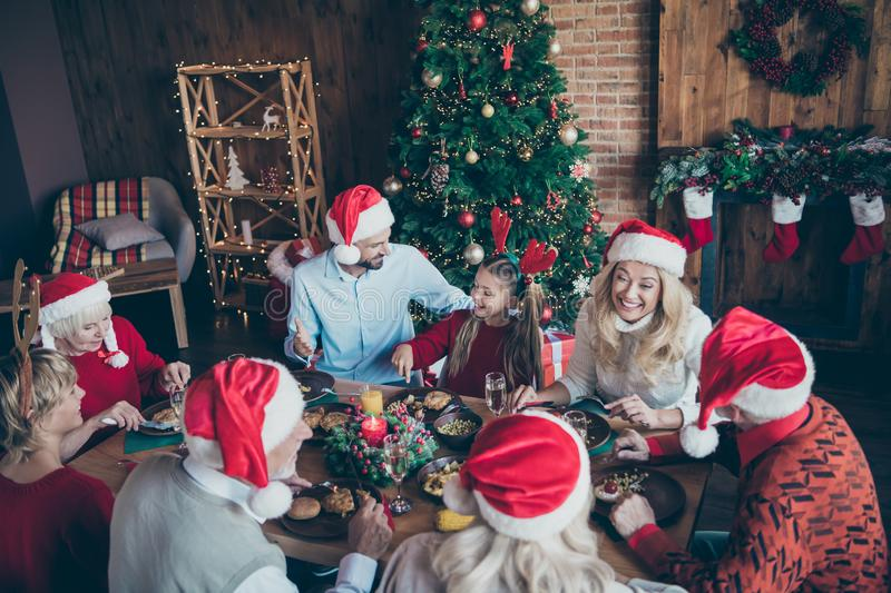 Top high angle photo of large family wear santa claus hat cap meeting on x-mas eve sit table eat talk speak among. Top high angle photo of large family wear stock images