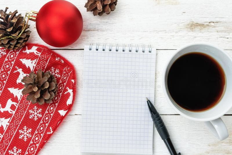 Top image of open notebook with blank pages, next to pine cones, red Christmas ball and cup of coffee over wooden table stock photos