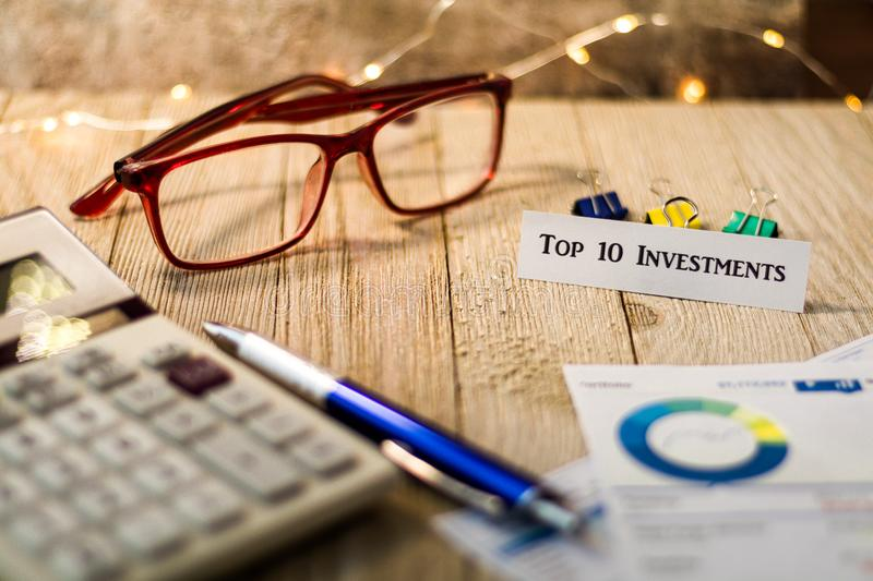 Top 10 Investments motivational concept on wooden board. Investment Strategy motivational concept with charts and graphs and calculator on wooden board and royalty free stock photo