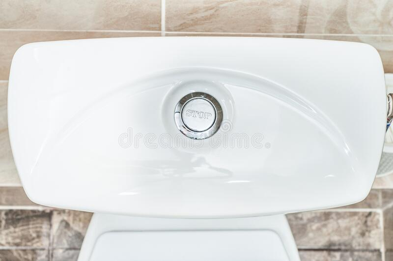 Top lid of the toilet drain tank with a water release button.  stock images