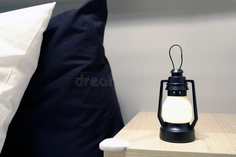 Top lights, bedside chest. A bedside rug. Bed soft blanket pillows. The atmosphere of coziness stock image