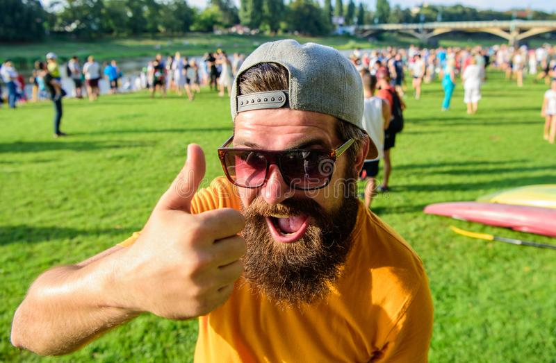 Top list summer festival must visit. Highly recommend top list. Hipster visiting event picnic fest or festival. Man. Bearded in front of crowd riverside royalty free stock photos