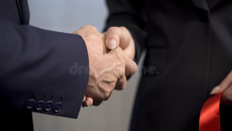 Top manager shaking hands with female business partner after ribbon cutting royalty free stock image
