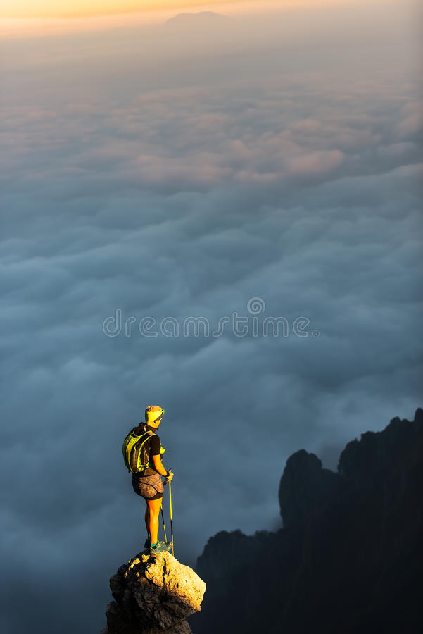 On top of a mountain spire with clouds sea. A person rests while ago a trek and observe the spectacle from the top stock images