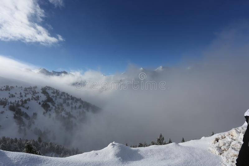 The top of the mountains with forest covered with snow, fog and clouds on a sunny frosty day. The top of the mountains with forest covered with snow stock images