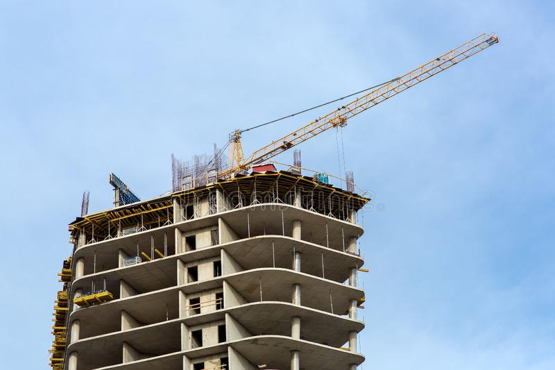 The top of a multi-story high-rise building under construction. The top of a multi-story high-rise building under construction under the sky with yellow crane stock image