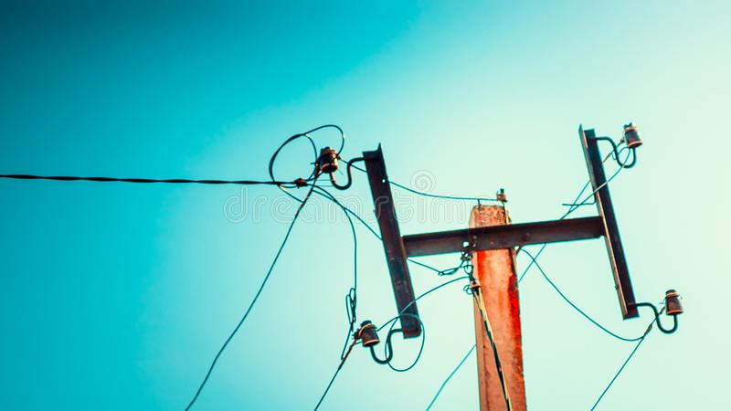 Top old electrical pillar on a background of the blue sky stock image