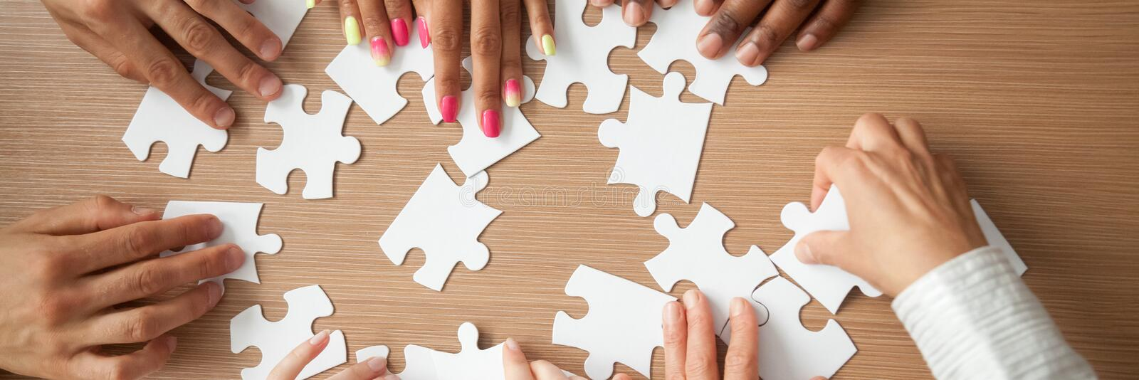 Top panoramic view hands of multinational people assembling jigsaw puzzle stock images