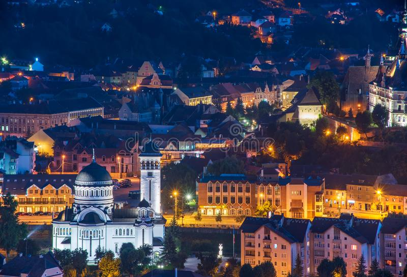 Top panoramic view of illuminated orthodox church and old buildings in downtown of Sighisoara, Romania at night stock photos